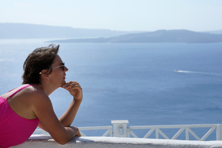 Woman with Fuchsia dress and the Oia Caldera Scenery as a background