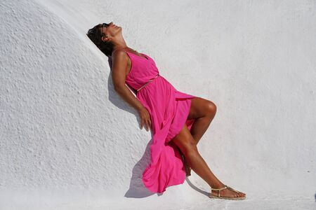 Woman with fuchsia dress relaxes by a small church of Oia in Santorini, Greece
