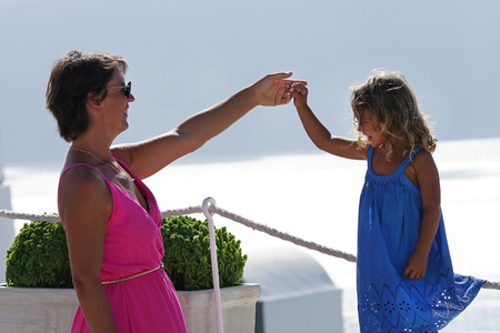 Woman with fuchsia dress plays with her little daughter on Oia Scenery as a background in Santorini, Greece