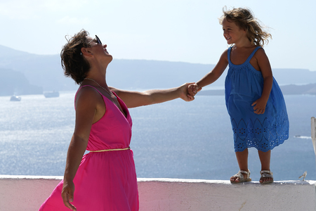 The woman in the fuchsia dress plays with a 3-4 years old girl, with the Oia Caldera Scenery as a background in Santorini, Greece
