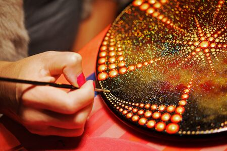Drawing with a brush a mandala on round board closeup