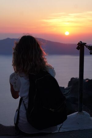 Tourist admire the sunset from Imerovigli
