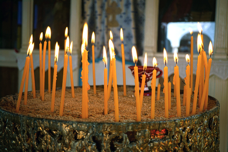 Votive candles lit in a small Orthodox church in Greece Stock Photo