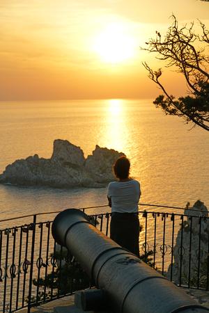 Un turista admira la hermosa vista de una puesta de sol desde el monasterio de la Virgen María al atardecer
