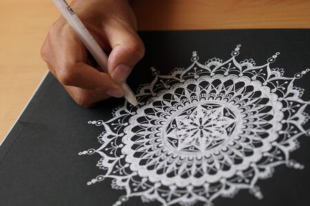 Draw a white mandala with a pencil on a black background
