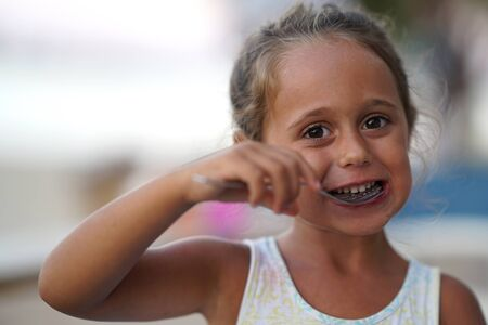 Adorable 4 year old girl eating and smiling.