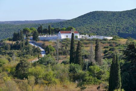 Small and picturesque church with cemetery on the rolling hills of central kythira in Greece Stock fotó