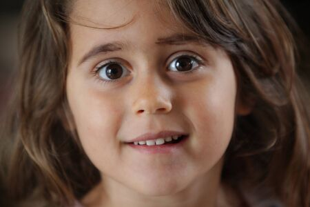 4 and a half year old girl looking with big eyes at the camera
