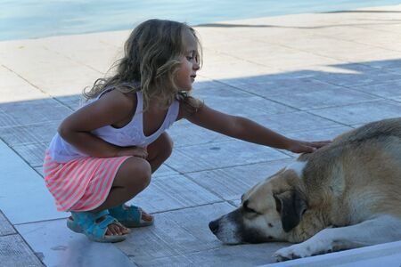 Blonde 4 year old girl caresses a street dog