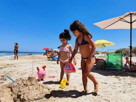 Torre Rinalda, Lecce June 14, Two girls play on a beach in Salento in Italy