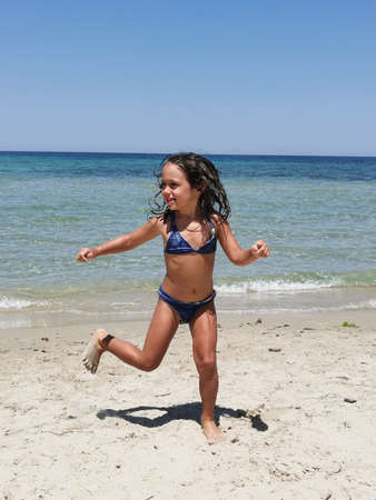 one little girl plays on a beach in Salento in Italy 版權商用圖片