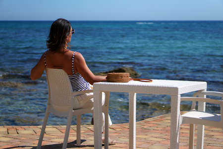 A woman is sitting in an outdoor cafe near the sea in Italy
