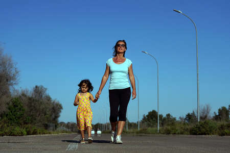 a mother and her little daughter walk on a road Banque d'images