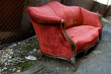 Abandoned Red Couch in an Alley Stock Photo