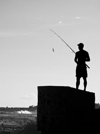A Man Stands on a Wall Hopeful of Making the Big Catch