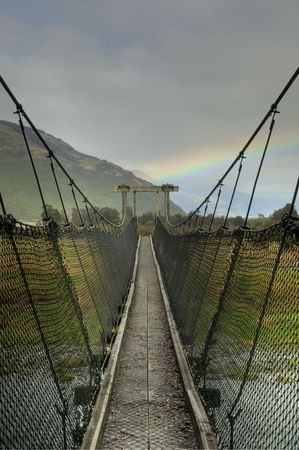 A footbridge leading towards a beautiful rainbow