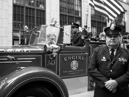 CIUDAD de nueva YORK, Estados Unidos - el 11 de octubre de 2010: Un funcionario se encuentra en frente de su cami�n de fuego en el desfile del d�a de Col�n en la Quinta Avenida. Editorial