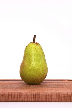 A Single Pear on a Cutting Board Isolated against a White Background