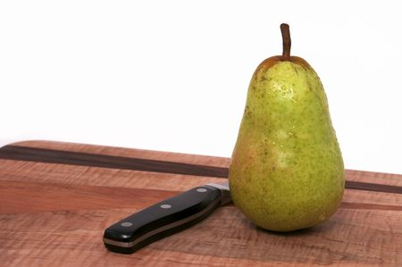 A Single Pear on a Wood Cutting Board with Black Knife Isolated against a White Background
