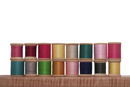 Stacked Spools of Colorful Thread on a White Background
