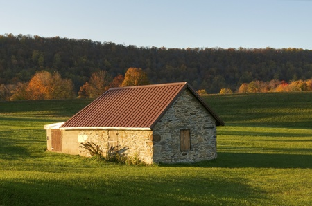 An old stone building surrounded by green during autumn