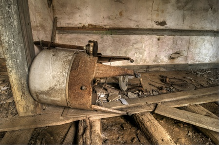 An old piece of household equipment lies in an abandoned house