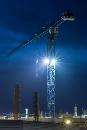 Tall lifting crane and construction at dark blue sky background  Vertical orientation photo