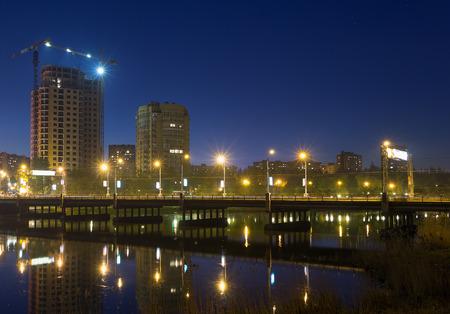 Illuminated bridge road over Kalmius river in Donetsk, Ukraine. Reflections in water. Construction. Stock Photo