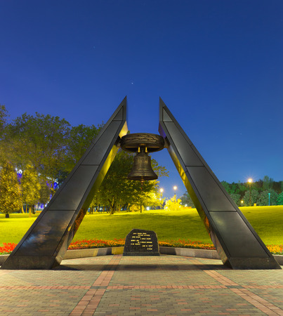Memorial monument for Defenders of Donbass, big bell, dark granite stone with text in center  Park with green grass, trees and stadium behind  Blue night sky