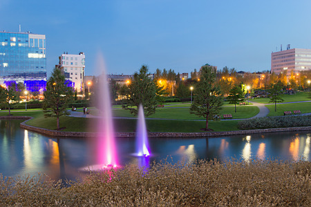 Fountains with purple and lilac backlight in park near Donbass Arena Stadium in Dontesk, Ukraine. Clear blue sky. Evening time. Stock Photo