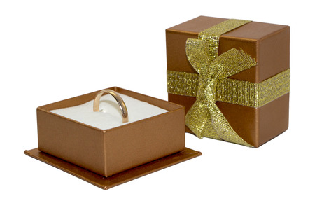 Golden wedding ring in open gift box, box cover with ribbon and bow, isolated on white background Stock Photo
