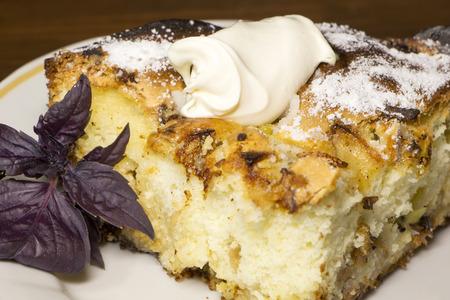 casa de campo: Pedazo de empanada dulce con crema agria en él y hojas de albahaca cerca de él en la placa blanca. Empanada con requesón, pasas, nueces, manzanas y kiwi en ella.