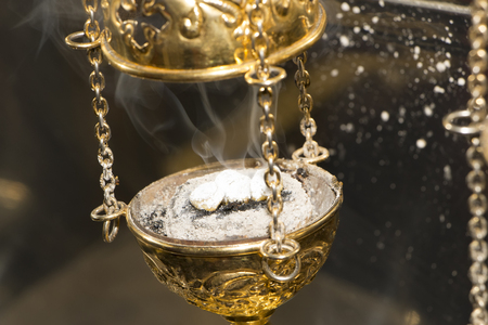 Christian Church brass thurible liturgy censer with coal, ash, smoke and incense in it. Closeup. Selective focus. Stock Photo
