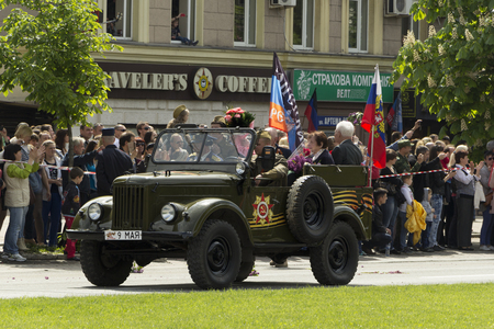 Donetsk People Republic, Ukraine. 2016, May 9. - Russian military veterans of World War II riding in the old car along Artema street during Victory Parade in Donetsk. The crowd photographs show. Flowers, Flags of Russia and DPR.