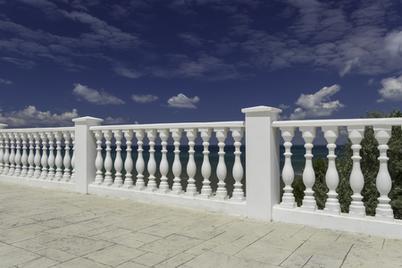 White decorative fence on the waterfront of the city of Anapa resort on the Black Sea coast. Blue cloudy sky, water with an emerald hue. Stock Photo