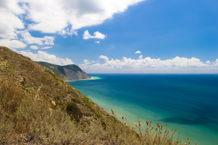Beautiful mountain view on Black sea beach from the top of hilll. Azure water, blue cloudy sky. Hill with dry grass in foreground. Stock Photo