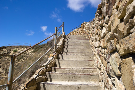 Concrete stairs ascending to top of hill. Bright blue sky over the hill. Rock wall, handrail and dry grass. Close up. Selective focus on stairs. Stock Photo
