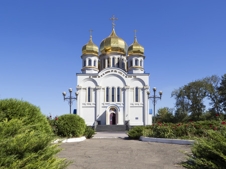 Orthodoxy church temple with golden domes: Holy Protection of the Mother of God. Front view. Greenery with red roses and blue sky around it. Donetsk, Ukraine, 2016.