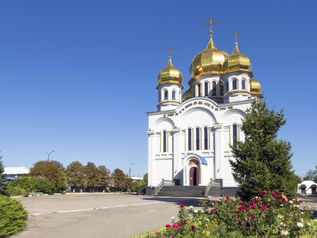 Orthodoxy church temple with golden domes: Holy Protection of the Mother of God. Angle view. Greenery with red roses and blue sky around it. Donetsk, Ukraine, 2016.