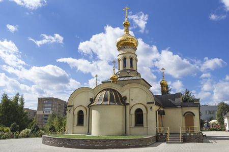 Temple of Xenia of St. Petersburg in Donetsk, Ukraine, 2016. Orthodox church. Golden domes and crosses under blue sky.