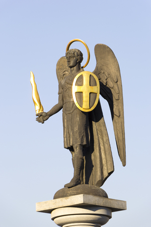 Statue of Saint Michael the Archangel with golden sword and shield near Holy Transfiguration Cathedral in Donetsk, Ukraine - 2016, September 11. Close up. Clear blue sky in the background. Editorial