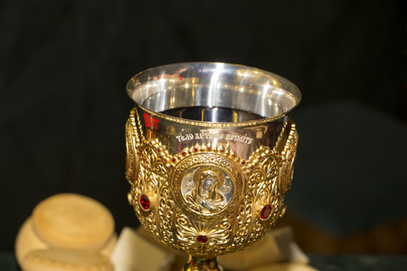 Chalice with red wine for communion, holy bread, preparation before Divine Liturgy in the Orthodox Church. Inscription Receive the Body of Christ and Mother of God icon. Close-up photo, dark background.