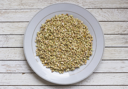 Sprouted buckwheat in white plate on white wooden table. Top view. Center position. Organic raw hulled groats. Close up background with copy space. Concept of healthy nutrition. Vegan food. Banque d'images