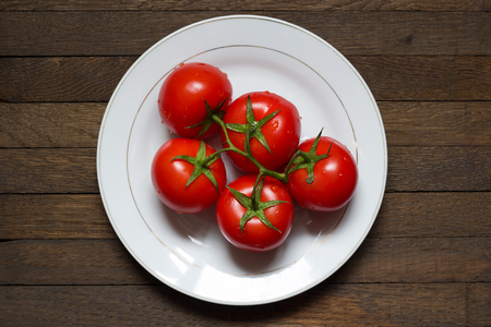 Washed juicy red tomatoes on white plate on dark brown wooden background. Top view. Healthy meal concept. Raw foods. Water droplets on fresh vegetables on green branch. 写真素材