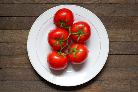 White plate with red washed ripened tomatoes on wooden table with copy space. Top view. Center position. Water droplets on vegetables. Close up background. Raw foods. Healthy nutrition concept.