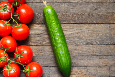 Ripe red tomatoes with cucumber on wooden desk. Top view. Water drops on washed vegetables. Fresh raw food. Agriculture background. Close up. Copy space.