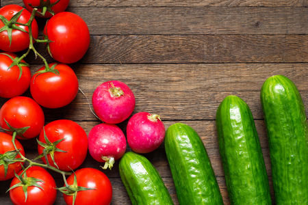 Green cucumbers with red ripe tomatoes and radishes on wooden desk. Top view. Copy space. Water drops on washed vegetables. Fresh raw food. Agriculture background. Close up.
