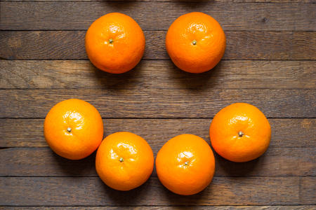 Positive raw foods concept. Mandarins laid out in the smile shape on dark wooden table. Healthy nutrition and positive lifestyle concept. Top view. Close up.