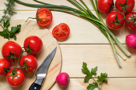 Healthy food cooking concept. Fresh tomatoes on branch, radish, onion, dill and parsley laid out on rustic light wooden table. Knife on kitchen board. Top view. Natural organic ingredients.