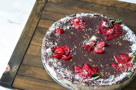 Delicious chocolate homemade vegan cake on wood tray. Healthy sweets. Raw foods. Natural chocolate, sprinkled with carob powder and coconut chips. Strawberries, cocoa butter, nutty basis. Top view. Banque d'images - 122194923